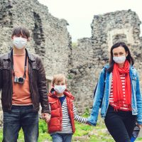 Family walking near castle ruins. Travelling during coronavirus pandemic. Parents with son wearing face masks outdoors. Safety mask to protect virus. Coronavirus quarantine. Family trip to old castle.